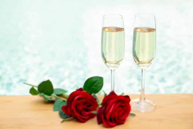 Dwa kieliszki do szampana z kwiatem róży następnego basenu. Premium Zdjęcia