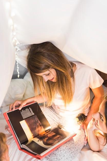 Dwa kobiet czytelniczy magazyn z iluminującą latarką na łóżku Darmowe Zdjęcia