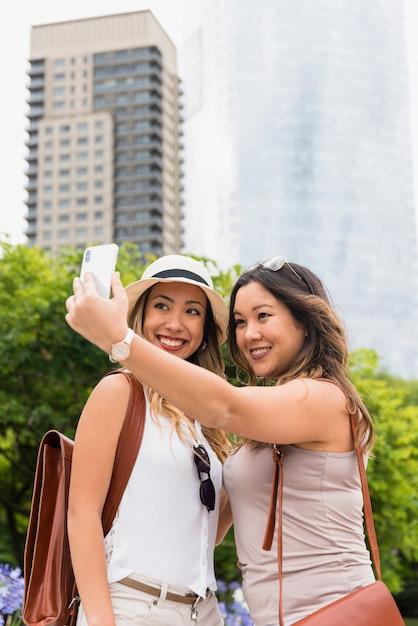 Dwa kobiet turysta z ich plecakiem bierze selfie na telefonie komórkowym przy outdoors Darmowe Zdjęcia