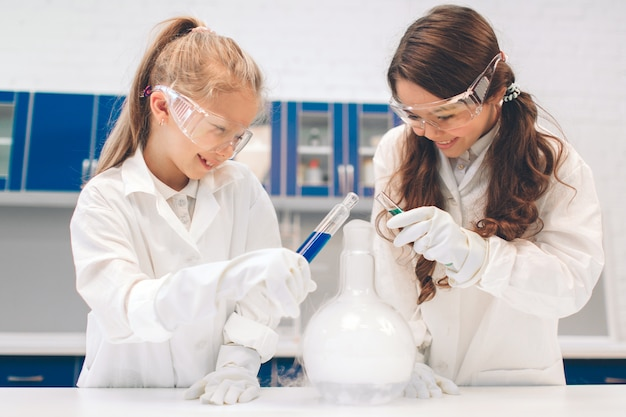 Dwa Małe Dzieci W Fartuchu Nauki Chemii W Szkolnym Laboratorium. Badanie Składników Do Eksperymentów. Niebezpieczne Eksperymenty. Premium Zdjęcia