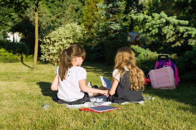 Dwa Małych Dziewczynek Przyjaciół Uczennica Uczy Się Siedzieć Na łące W Parku Premium Zdjęcia