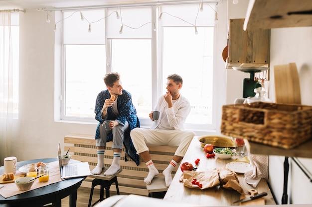Dwa męski przyjaciel siedzi w kuchni je śniadanie Darmowe Zdjęcia