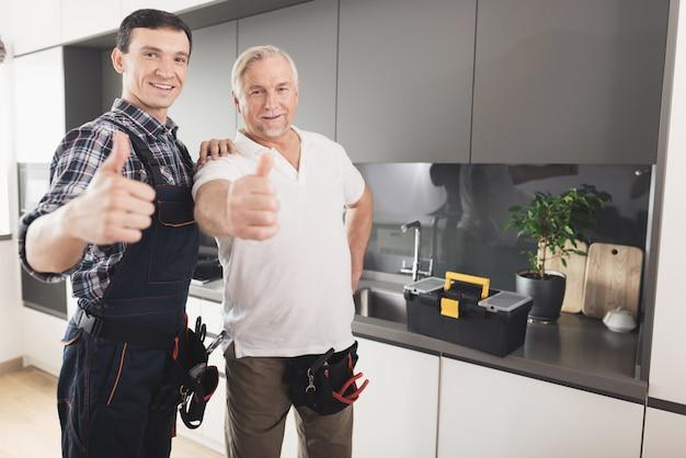 Dwa męskiego hydraulika pozuje w nowożytnej kuchni Premium Zdjęcia