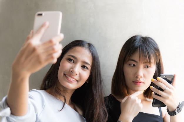 Dwa młoda azjatykcia dziewczyna używa telefon komórkowego ono selfie Premium Zdjęcia