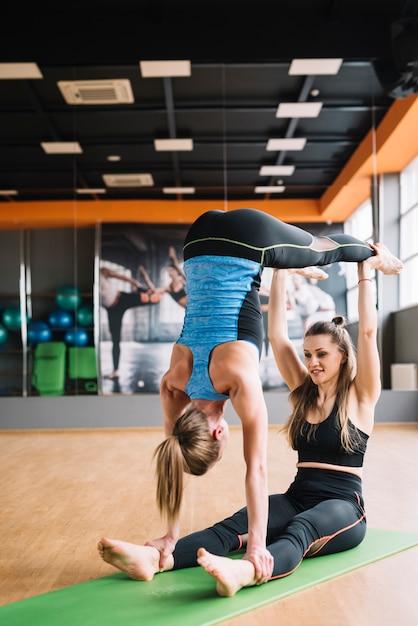 Dwa młoda kobieta robi acro joga w gym Darmowe Zdjęcia