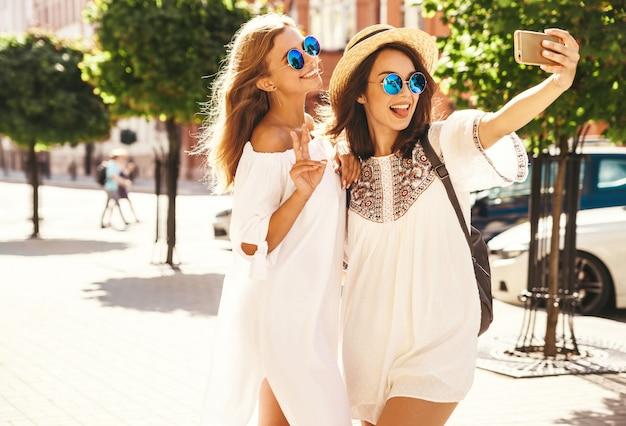 Dwa Młodego żeńskiego Uśmiechniętego Hipisa Brunetki I Blond Kobiet Modelki W Lato Słonecznym Dniu W Białych Modnisiach Odziewają Brać Selfie Fotografie Dla Społecznościowych Na Telefonie. Pokazywanie Pokoju Darmowe Zdjęcia