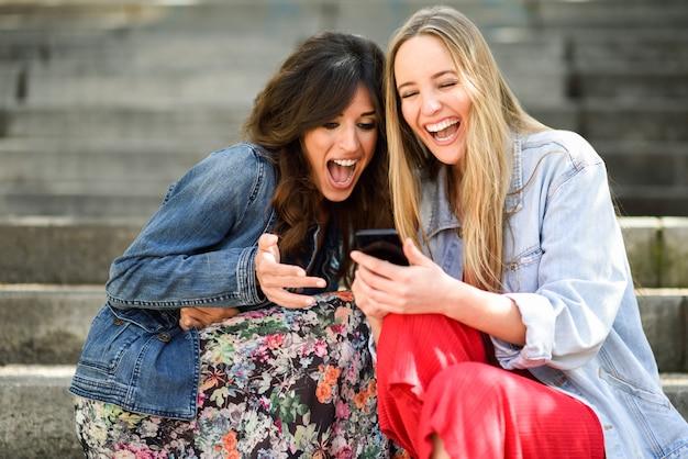 Dwa Młodej Kobiety Patrzeje Niektóre śmieszną Rzecz Na Ich Mądrze Telefonie Outdoors Darmowe Zdjęcia