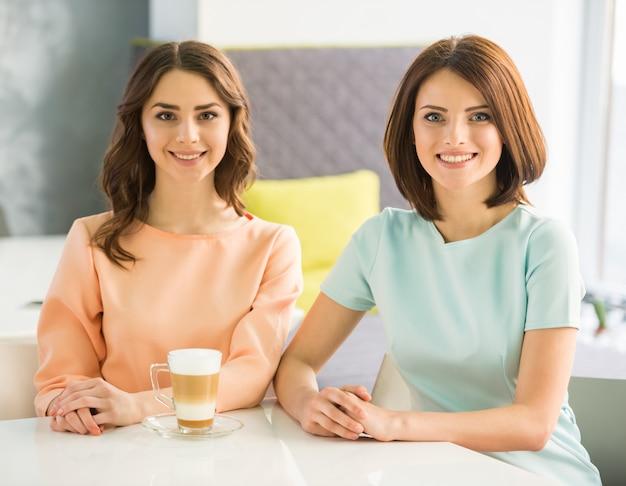 Dwa młodej pięknej uśmiechniętej dziewczyny siedzi w miastowej kawiarni. Premium Zdjęcia