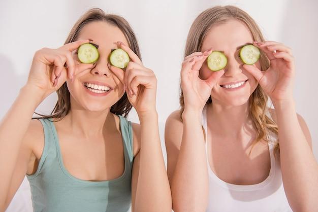 Dwa Młodych Uśmiechniętych Dziewczyn Kładzenie Na Oko Ogórku. Premium Zdjęcia