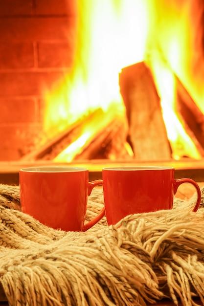 Dwa pomarańczowe kubki na herbatę lub kawę, rzeczy z wełny na tle przytulnego kominka. Premium Zdjęcia