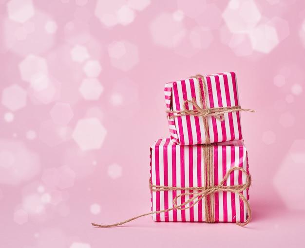 Dwa Pudełka Owinięte W świąteczny Różowy Papier I Przewiązane Brązową Liną Premium Zdjęcia