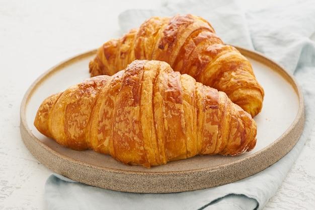 Dwa Pyszne Rogaliki Na Talerzu I Gorący Napój W Kubku. Rano Francuskie śniadanie Ze świeżymi Wypiekami Premium Zdjęcia