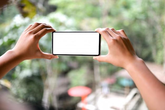 Dwa Ręki Trzyma Smartphone Pustego Ekran Z Naturą Zamazywali Widok Tło. Premium Zdjęcia