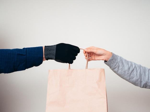Dwa Ręki Z Papierową Torbą Na Białym Tle. Koncepcja Dostawy Pandemii Covid-19. Premium Zdjęcia