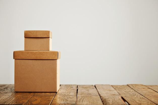 Dwa Różnej Wielkości Beżowe Pudełka Z Tektury Falistej Bez Etykiet, Umieszczone Jeden Na Drugim, Na Białym Tle Darmowe Zdjęcia