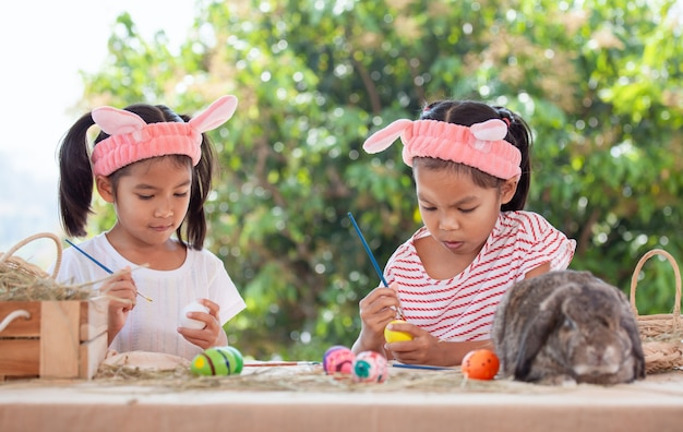 Dwa ślicznej Azjatykciej Dziecko Dziewczyny Rysuje I Maluje Na Easter Jajkach Wpólnie Przygotowywają Dla Easter Dnia Premium Zdjęcia