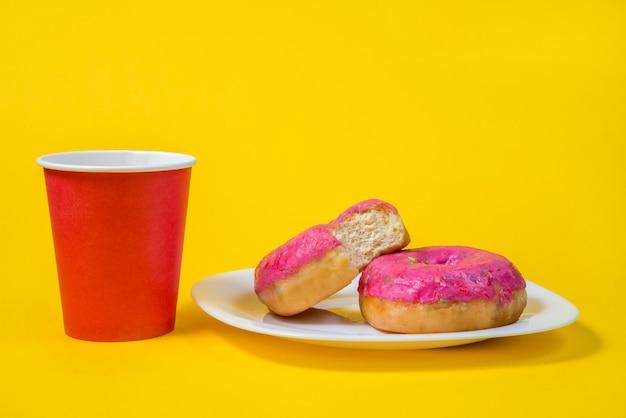 Dwa słodkie pół zjedzone różowe pączki na białym talerzu na białym tle na żółtym tle Premium Zdjęcia