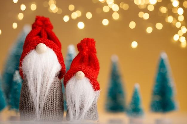 Dwa świąteczne Krasnale W Czerwonych Kapeluszach Na Złotym Tle Premium Zdjęcia