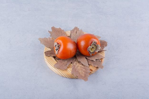 Dwa świeże Owoce Persimmon I Suszone Liście Na Drewnianym Talerzu. Darmowe Zdjęcia
