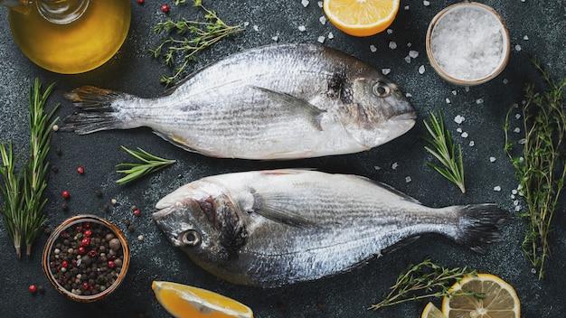 Dwa świeże surowe ryby dorado z przyprawami i oliwą z oliwek na ciemnym stole z kamienia. widok z góry. leżał płasko. Premium Zdjęcia