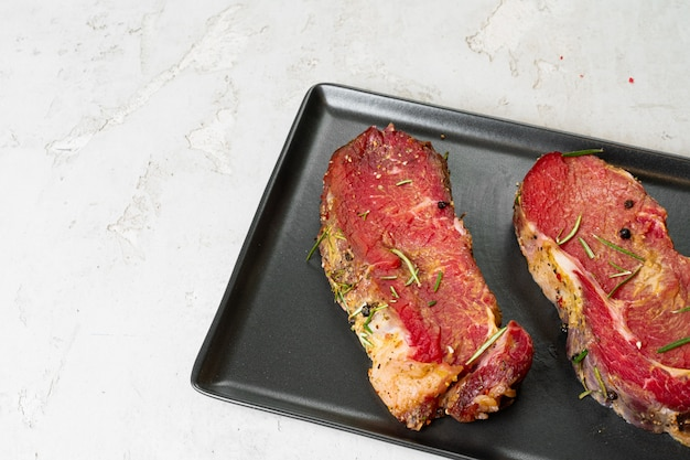 Dwa świeżego Surowego Mięsa Na Czarnym Talerzu Ceramicznym Premium Zdjęcia