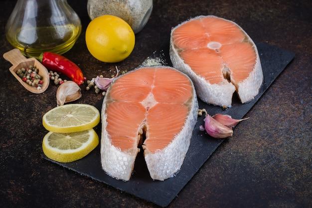 Dwa świeżego surowego stku łososia na desce łupku z solą, papryką, cytryną na ciemnym stole, widok z góry. koncepcja zdrowej diety Premium Zdjęcia