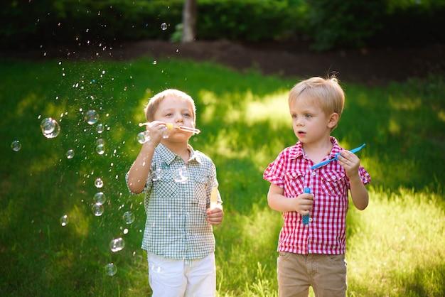 Dwa Szczęśliwa Chłopiec Bawić Się W Bąblach Outdoors Premium Zdjęcia
