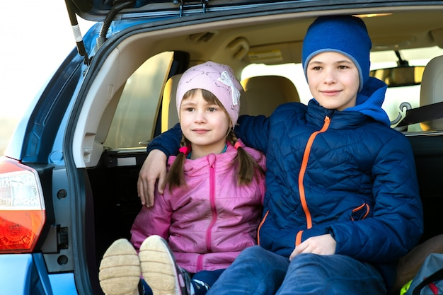 Dwa Szczęśliwego Dziecka Chłopiec I Dziewczyna Siedzi Wpólnie W Bagażniku Samochodu. Wesoły Brat I Siostra Przytulający Się Do Bagażnika Pojazdu Rodzinnego. Weekendowa Podróż I Wakacje Pojęcie. Premium Zdjęcia