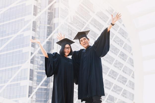 Dwa szczęśliwego ucznia świętuje pomyślnego skalowanie na kampusu budynku tle Premium Zdjęcia