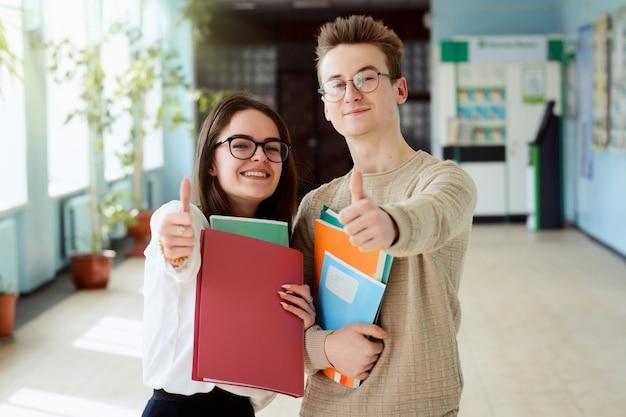 Dwa szczęśliwego ucznia w dobrym nastroju pokazuje aprobaty Premium Zdjęcia