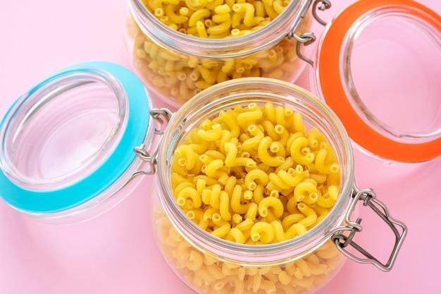 Dwa Szklane Słoiki Z Surowym Makaronem. Garnki Z żółtym Makaronem Premium Zdjęcia