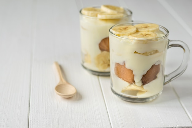 Dwa Szklanego Kubka Z Budyniem Bananowym I Drewnianą łyżką Na Białym Stole. Deser Mleczny I Bananowy. Premium Zdjęcia