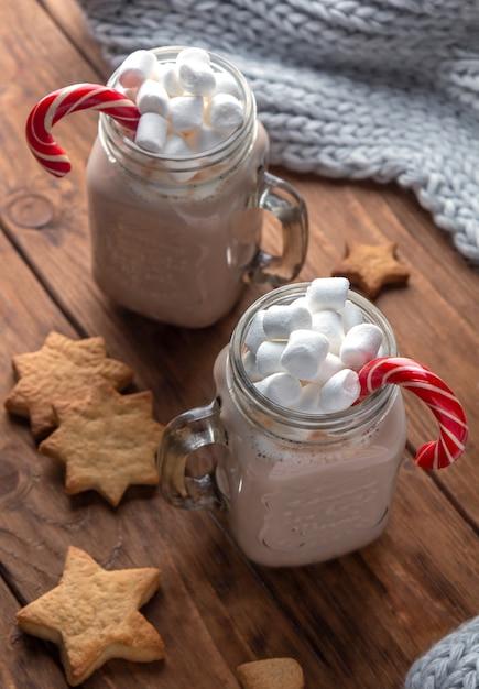 Dwa Szklanego Kubka Z Kakao, Piankami, Trzciny Cukrowej I Imbirowymi Ciastkami Na Drewnianym Tle. Premium Zdjęcia