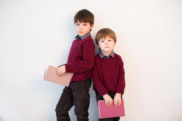 Dwa Ucznia Czytają Książki Na Białym Tle W Studiu. Premium Zdjęcia