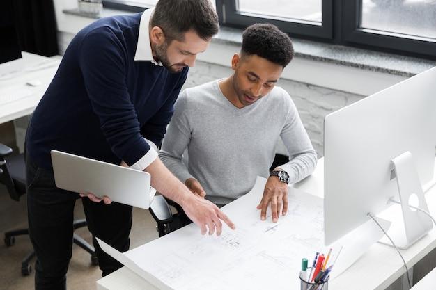 Dwa Uśmiechniętego Męskiego Urzędnika Pracuje Z Laptopem Darmowe Zdjęcia