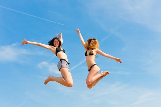 Dwa uśmiechniętej kobiety w swimwear skacze wysoko w niebie Premium Zdjęcia