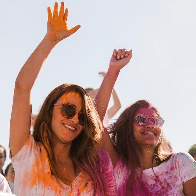 Dwa Uśmiechniętej Młodej Kobiety Z Holi Kolorem Na Ich Twarzy Tanczy Wpólnie Darmowe Zdjęcia