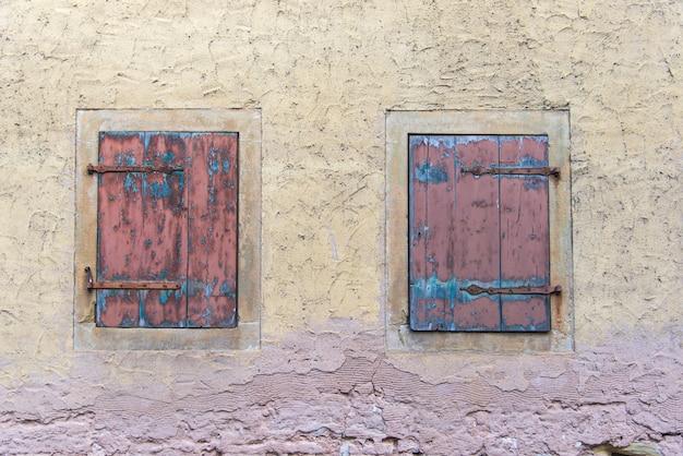 Dwa Woody Okna Na Klasycznej Plae żółtej Starej ścianie W Europie Premium Zdjęcia