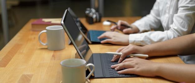 Dwa żeńskiego Pracownika Pracuje Nad Ich Projektem Z Cyfrową Pastylką Podczas Gdy Siedzący Wpólnie W Biurowym Pokoju Premium Zdjęcia