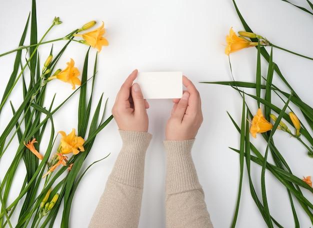 Dwa żeńskiej Ręki Trzyma Pustą Białą Papierową Kartę I żółte Leluje Premium Zdjęcia