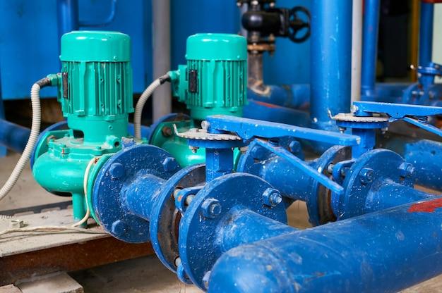 Dwa zielone przewody elektryczne pompy wody w kolorze niebieskim. Premium Zdjęcia
