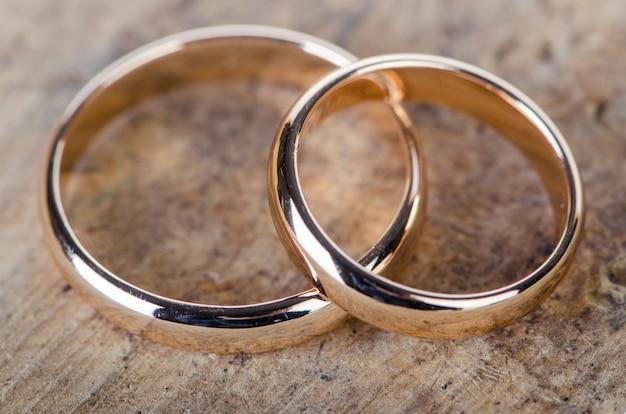 Dwa Złote Obrączki Na Drewniane Tła Premium Zdjęcia
