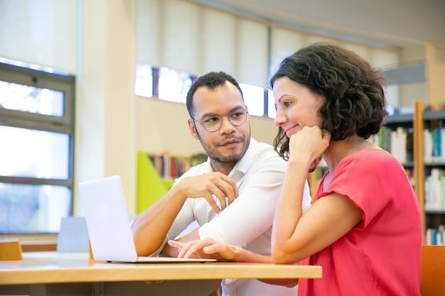Dwaj koledzy pracujący nad prezentacją w bibliotece Darmowe Zdjęcia