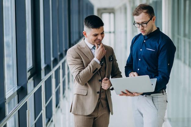 Dwaj Koledzy W Biurze, Stojąc Z Laptopem Darmowe Zdjęcia