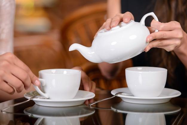 Dwaj Przyjaciele Piją Herbatę I Rozmawiają W Kawiarni. Premium Zdjęcia