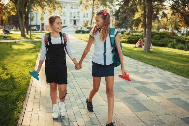 Dwaj Szkolni Przyjaciele Chodzą Po Lekcjach W Parku W Pobliżu Szkoły Premium Zdjęcia