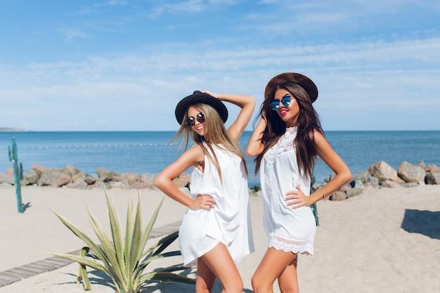 Dwie Atrakcyjne Brunetki I Blond Dziewczyny Z Długimi Włosami Siedzą Na Plaży W Pobliżu Morza. Pozują Do Kamery. Darmowe Zdjęcia