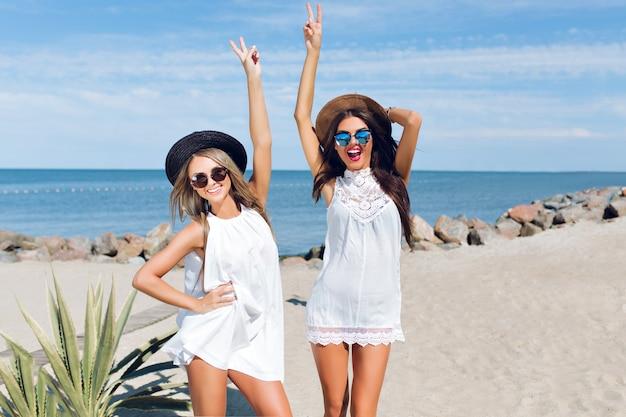 Dwie Atrakcyjne Brunetki I Blond Dziewczyny Z Długimi Włosami Siedzą Na Plaży W Pobliżu Morza. Trzymają Ręce Powyżej, Pozują I Uśmiechają Się Do Kamery. Darmowe Zdjęcia