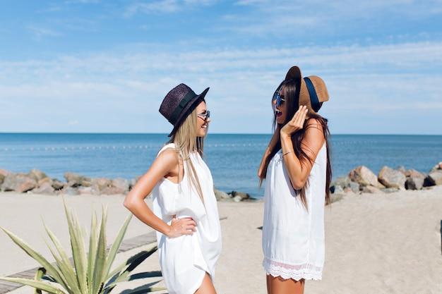 Dwie Atrakcyjne Brunetki I Blond Dziewczyny Z Długimi Włosami Stoją Na Plaży W Pobliżu Morza. Rozmawiają Ze Sobą. Darmowe Zdjęcia