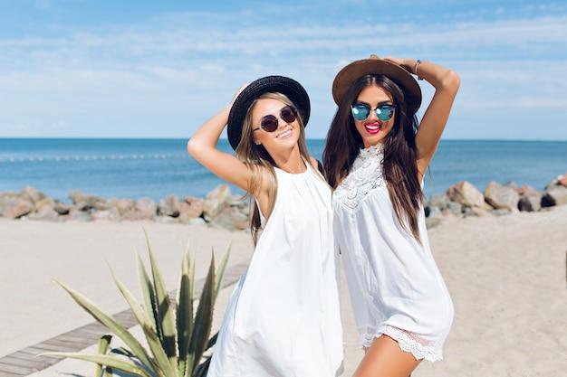 Dwie Atrakcyjne Brunetki I Blond Dziewczyny Z Długimi Włosami Stoją Na Plaży W Pobliżu Morza. ściskają Się I Uśmiechają Do Kamery. Darmowe Zdjęcia
